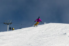 Female skier carving down an Australian ski slope. On a cloudy day. A dormant snow gun and chair lift can be seen in the background Royalty Free Stock Photography