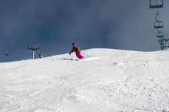 Female skier carving down an Australian ski slope. Between two chair lifts. A dormant snow gun can be seen in the background Royalty Free Stock Photography