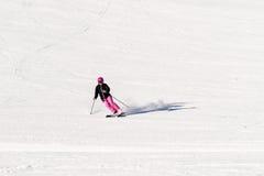 Female skier on empty ski slope. Action shot of a female sportive middle aged skier on empty ski slope Royalty Free Stock Image