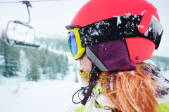 Female skier enjoying beautiful mountain scene. Close-up portrait of female skier in safety helmet and mask enjoying beautiful mountain scene Royalty Free Stock Images