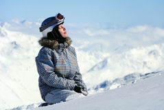 Female skier enjoying sun. Female skier wearing ski helmet is sitting in snow high up in Tirol Alps at Solden ski resort Royalty Free Stock Photography
