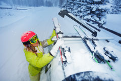 Female skier fastening skis to car roof`s rails Stock Images