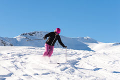 Female skier in fresh powder snow. Action shot of a female sportive middle aged skier in fresh powder snow Royalty Free Stock Photo