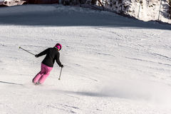 Female skier in fresh powder snow. Action shot of a female sportive middle aged skier in fresh powder snow speeding downhill towards a safety net Royalty Free Stock Images