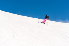 Female skier in fresh powder snow and blue sky. Action shot of a female sportive middle aged skier in fresh powder snow against great blue sky Stock Photo