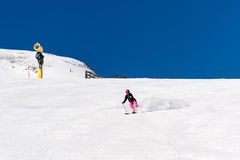 Female skier in fresh powder snow and blue sky. Action shot of a female sportive middle aged skier in fresh powder snow with snow cannon and blue sky in the Stock Images