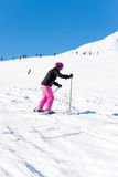Female skier in fresh snow. Action shot of a female sportive middle aged skier in fresh snow and bright sunlight with unidentifiable skiers in the background Stock Photography
