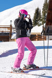 Female skier getting dressed in front of skiing hut stock image