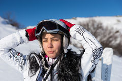 Female Skier with Hands Behind Head on Sunny Day. Waist Up Portrait of Young Woman with Long Dark Hair Squinting and Standing with Skis, Wearing Helmet and Stock Photo