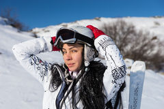 Female Skier with Hands Behind Head on Sunny Day. Waist Up Portrait of Young Woman with Long Dark Hair Standing with Skis and Wearing Helmet and Goggles with Royalty Free Stock Photos