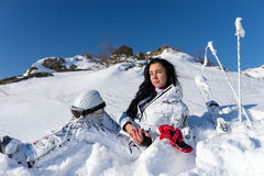 Female Skier with Helmet Enjoying Warm Sunshine. Full Length of Contented Young Woman with Long Dark Hair Holding Helmet and Goggles on Snow Covered Mountainside Stock Photography
