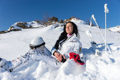 Female Skier with Helmet Enjoying Warm Sunshine. Full Length of Contented Young Woman with Long Dark Hair Holding Helmet and Goggles on Snow Covered Mountainside Stock Images