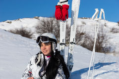 Female Skier in Helmet Sitting on Hill with Skis. Portrait of Young Woman with Long Dark Hair Wearing Helmet and Goggles While Sitting in Snow on Mountainside Stock Photos