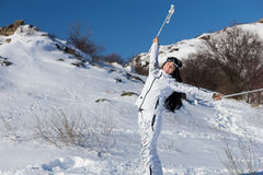 Female Skier Holding Poles Above Head on Hillside. Full Length Portrait of Smiling Young Woman with Long Dark Hair Taking a Break from Skiing and Holding Poles Royalty Free Stock Photos
