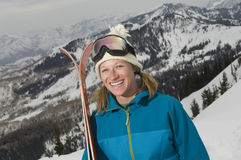 Female Skier Holding Skis On Mountain Royalty Free Stock Photography