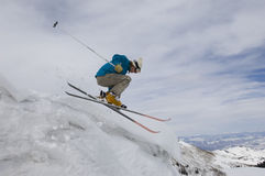 Female Skier Jumping Off Icy Overhang. Side view of a female skier jumping off icy overhang Royalty Free Stock Image