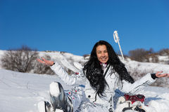 Female Skier with Open Arms Enjoying Warm Sun. Confident Young Woman with Long Dark Hair Sitting with Open Arms on Snow Covered Mountainside and Enjoying Warm Stock Image