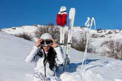 Female Skier Putting on Helmet Before Skiing. Young Woman with Long Dark Hair Putting on Helmet and Goggles While Sitting in Snow on Mountainside with Skis and Stock Photo