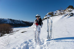 Female Skier Putting on Red Gloves on Mountainside Stock Image