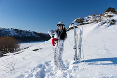 Female Skier Putting on Warm Mittens on Ski Hill. Full Length Candid Portrait of Woman with Long Dark Hair Standing on Snow Covered Mountainside with Skis and Royalty Free Stock Image