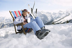 Female Skier Sitting On Deckchair In Mountains Royalty Free Stock Photo
