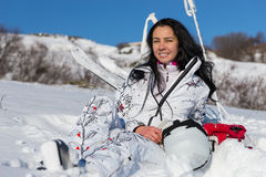 Female Skier Sitting and Enjoying Warm Sunshine. Full Length of Contented Young Woman with Long Dark Hair Sitting on Snow Covered Mountainside and Enjoying Warm Royalty Free Stock Images