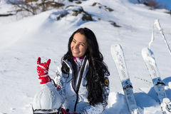 Female Skier Sitting on Hill Making Hand Gesture Royalty Free Stock Photo