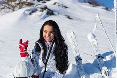 Female Skier Sitting on Hill Making Hand Gesture. Waist Up Portrait of Smiling Young Woman with Long Dark Hair Wearing White Ski Suit Sitting on Snow Covered Royalty Free Stock Photo