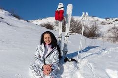 Female Skier Sitting on Snowy Hill with Skis. Portrait of Smiling Young Woman with Long Dark Hair Sitting on Snow Covered Mountain with Skis and Poles Nearby Stock Photography