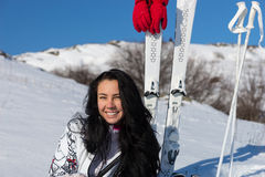 Female Skier Sitting on Snowy Hill with Skis. Portrait of Smiling Young Woman with Long Dark Hair Sitting on Snow Covered Mountain with Skis and Poles Nearby Royalty Free Stock Photo