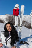 Female Skier Sitting on Snowy Hill with Skis. Portrait of Smiling Young Woman with Long Dark Hair Sitting on Snow Covered Mountain with Skis and Poles Nearby Royalty Free Stock Image