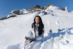 Female Skier Sitting on Snowy Hillside with Skis Stock Photography