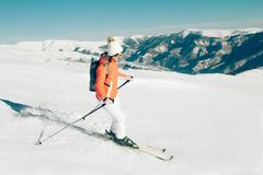 Female Skier skiing in mountain ski resort. Winter sport recreational activity. Outdoors Royalty Free Stock Photo