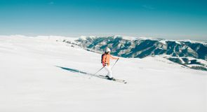 Female Skier skiing in mountain ski resort. Winter sport recreational activity. Outdoors Stock Photos
