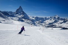 Female skier skiing on the slopes of Matterhorn mountain Stock Photo