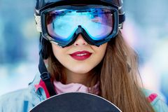 Female skier smiling and wearing ski glasses in the mountains. royalty free stock photography