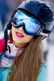 Female skier smiling and wearing ski glasses in the mountains. royalty free stock images