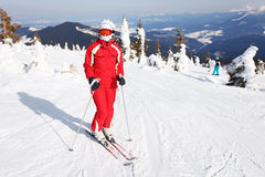 Female skier standing on mountain slope Royalty Free Stock Image