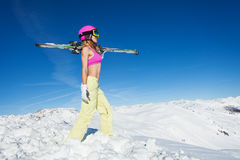 Female skier standing with skies on a snowy slope Royalty Free Stock Image