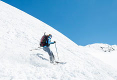 Female skier tackling a steep slope. Ski touring in the mountains Stock Images