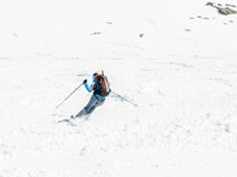 Female skier tackling a steep slope. Ski touring in the mountains Royalty Free Stock Photo