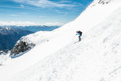 Female skier tackling a steep slope. Ski touring in the mountains Royalty Free Stock Photos