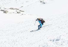 Female skier tackling a steep slope. Ski touring in the mountains Stock Image