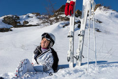 Female Skier Taking a Break on Snowy Mountainside. Full Length Portrait of Young Woman with Long Dark Hair Wearing Helmet and Goggles While Sitting in Snow on Stock Photography