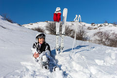 Female Skier Taking a Break on Snowy Mountainside. Full Length Portrait of Young Woman with Long Dark Hair Wearing Helmet and Goggles While Sitting in Snow on Stock Images