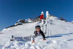 Female Skier Taking a Break on Snowy Mountainside. Full Length Portrait of Young Woman with Long Dark Hair Wearing Helmet and Goggles While Sitting in Snow on Royalty Free Stock Images