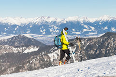 Female skier taking a look at landscape from the top of a mountain Royalty Free Stock Image