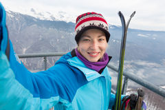Female skier taking selfie. Cheerful lady taking selfie enjoing the snowy mountain view, excited before skiing stock photo