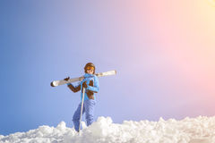 Female skier on top of the mountain against blue sky. Portrait of active female skier standing on top of the mountain against blue sky on a sunny day. Girl is Stock Photos