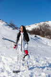Female skier walking up hill with equipment Royalty Free Stock Images